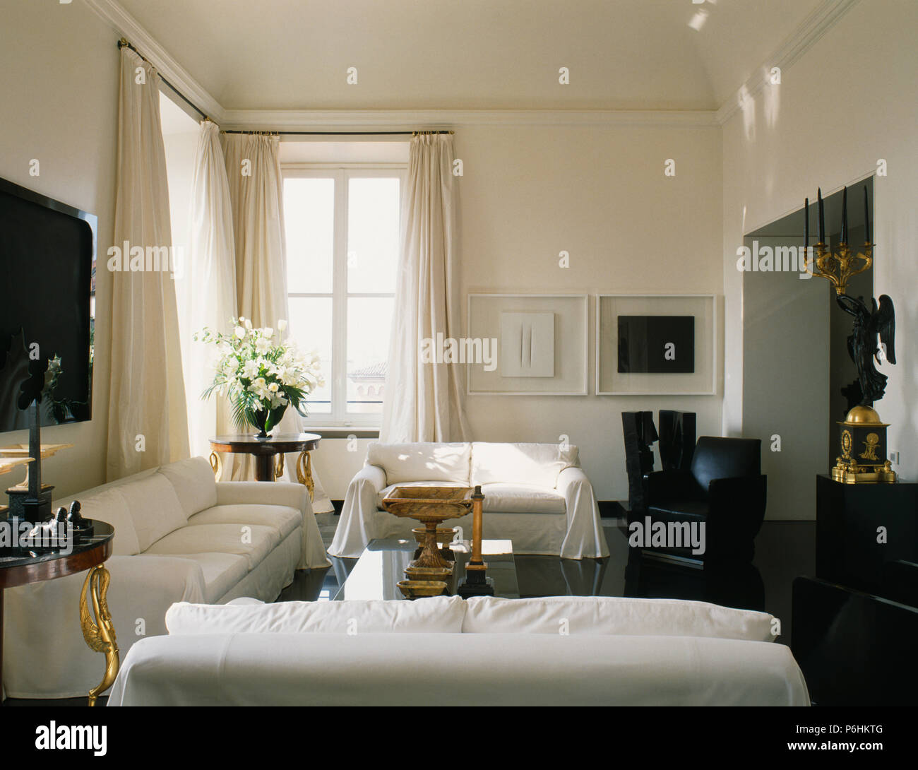 White Sofas In Modern White Apartment Living Room With White Cotton Drapes And Black Flooring Stock Photo Alamy