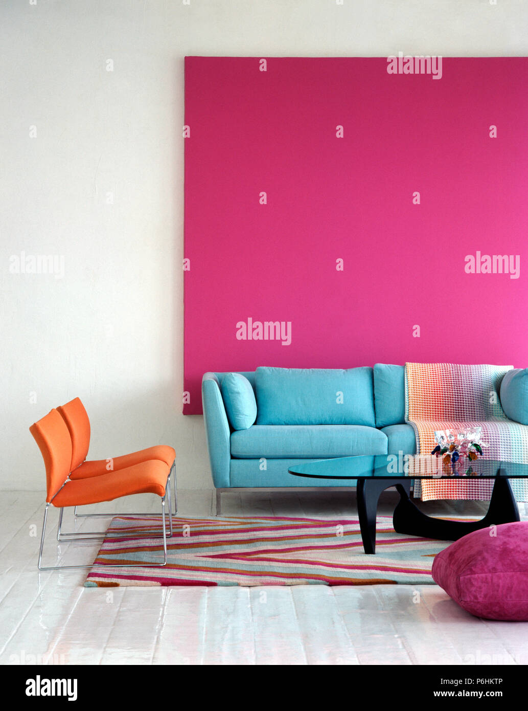 Superbe Pastel Blue Sofa Against Bright Pink Picture In Modern Living Room With  Orange Chairs And Glass Topped Coffee Table