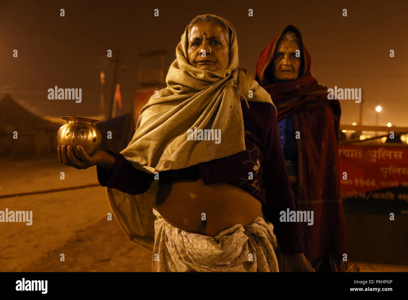 Two Hindu women are proudly showing a jug containing holy water from the Ganges river during pilgrimage  Maha Kumbh mela 2013 in Allahabad , India - Stock Image