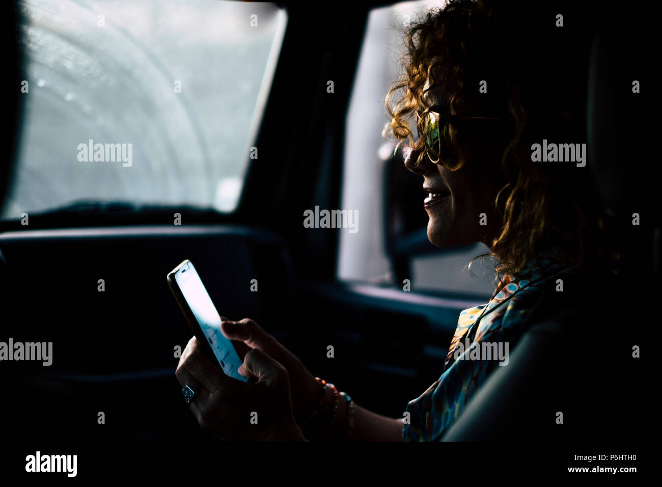 nice beautiful middle age woman travel inside a car shile rain outside. using a smartphone to connect and call friends and meet for the night to celeb - Stock Image