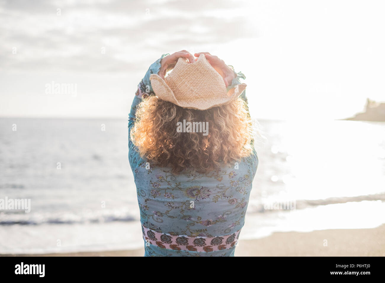 freedom young woman with cowboay hat in front of the ocean enjoying vacation and outdoor lifestyle. summer sunlight and waves and traveler spirit - Stock Image