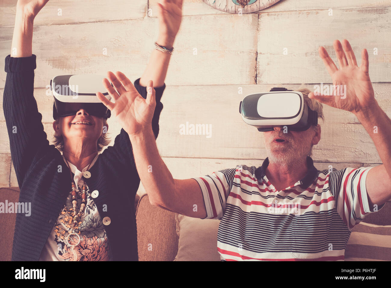 couple of senior adult caucasian enjoy technology with goggled headset and play in virtual realuty together having fun at home. trying new experience  - Stock Image