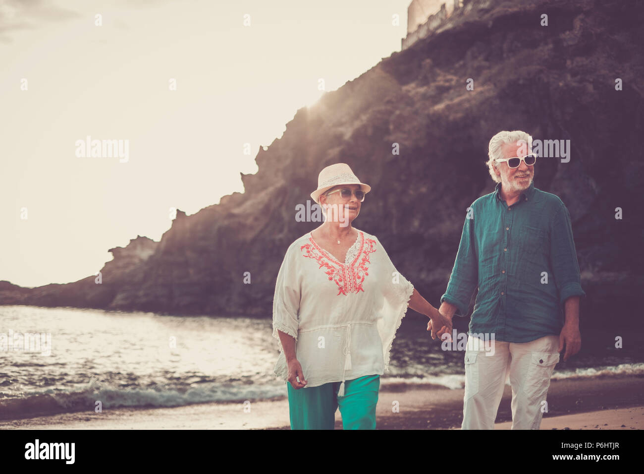 happy senior adult couple in love waing and smiling enjoying the summer time on the beach and the retired lifestyle of their new life together after y - Stock Image