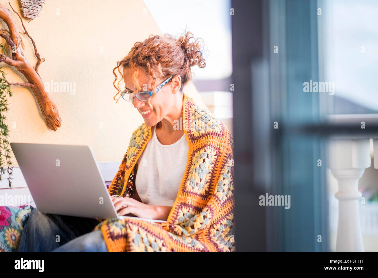 beautiful smiled caucasian woman work with a laptop computer outdoor in the terrace. alternative office and lifestyle working at home in totally freed - Stock Image