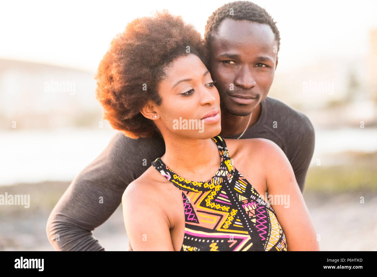 happy black race african couple at the beach in love and enjoying the leisure activity together sitting near the ocean coast summer time and loves vib - Stock Image