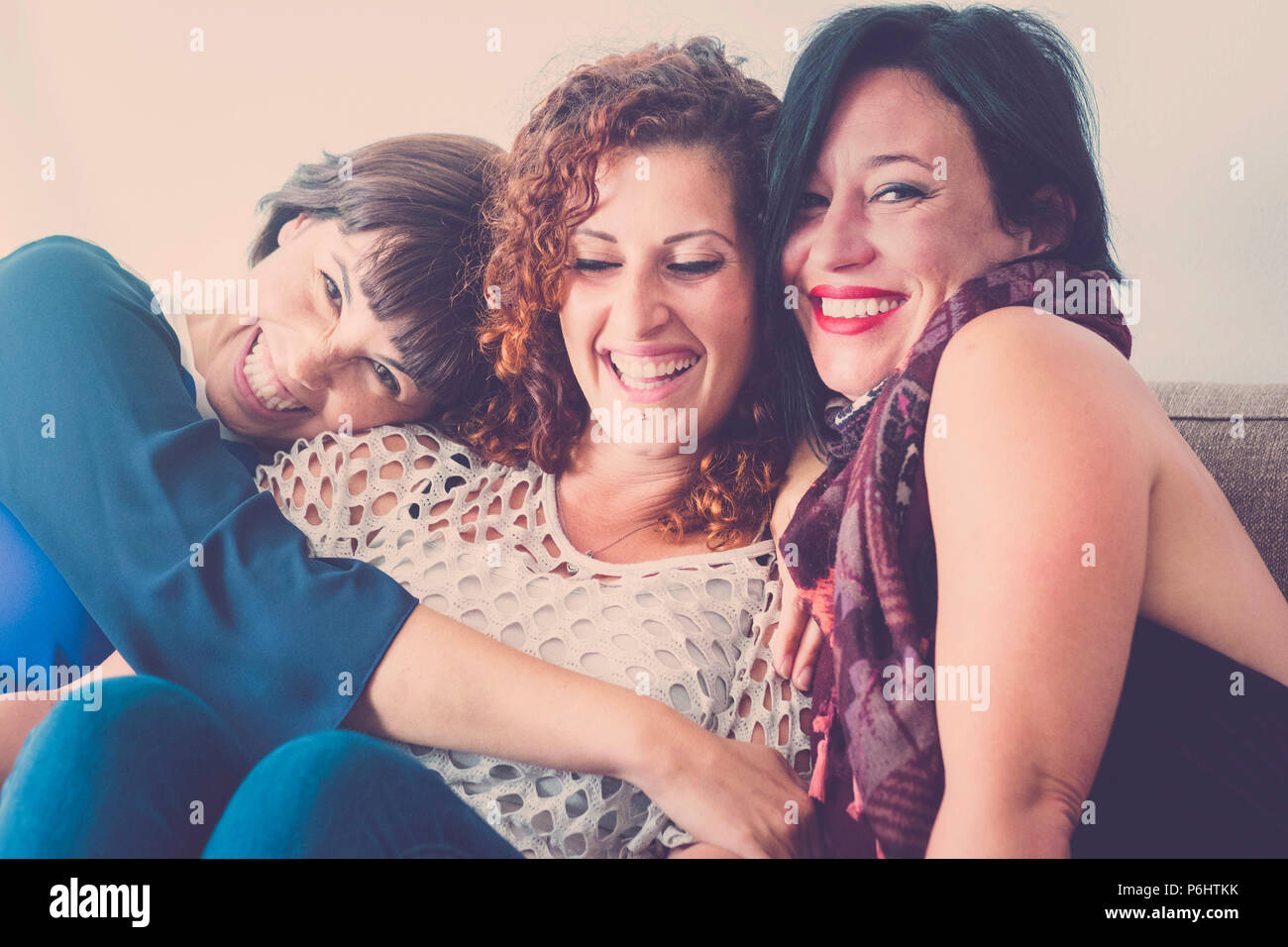 cheerful females middle age young womane friends together sitting on a sofa at home in leisure activity indoor. smile and enjoy the day hugging and to - Stock Image