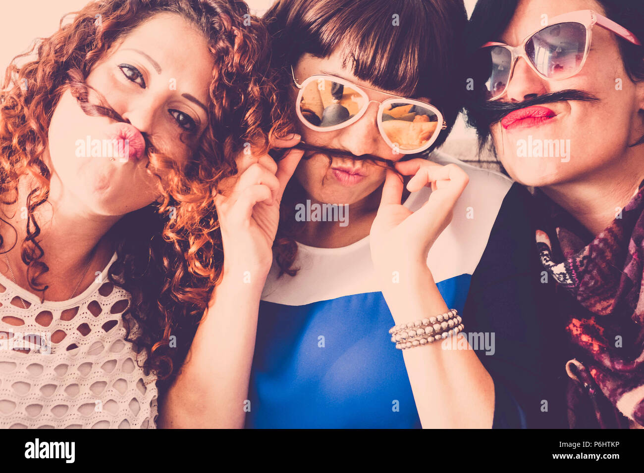three caucasian females friends stay together in friendship and craziness using hair like moustache and happiness relationship concept. vintage full c - Stock Image