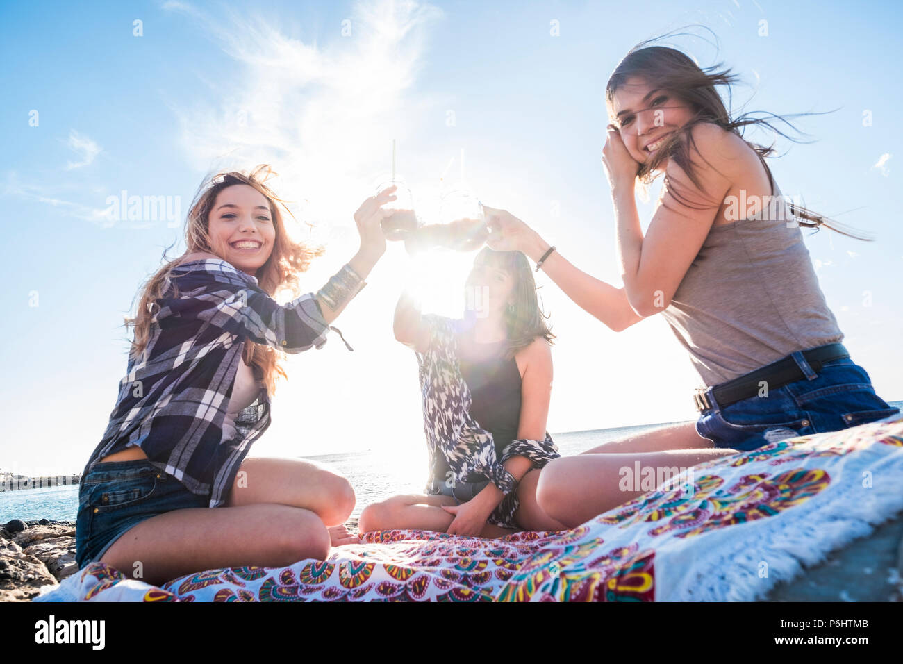 group of young women friend drinking together a fruit juice on a rock beach in Tenerife. Relationship for a team to enjoy the vacation and happiness.  - Stock Image