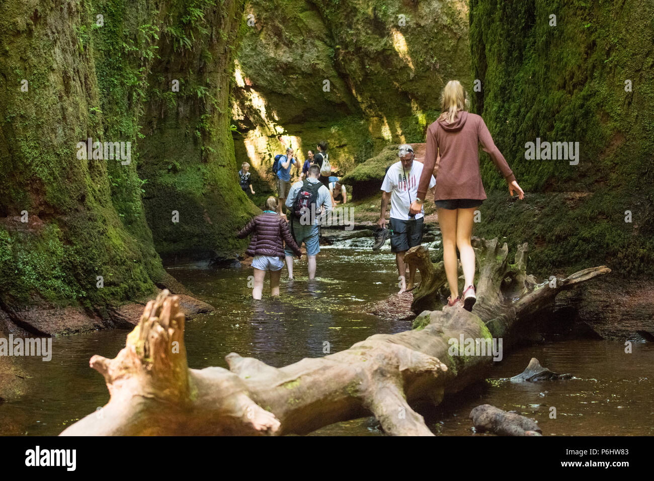 Tourists at Finnich Glen, Stirlingshire, Scotland - a beauty spot coming under increased pressure due to being used as a film location in Outlander - Stock Image
