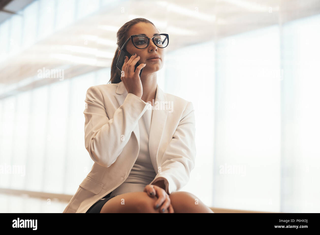 Young business spectacled woman in white jacket talking by mobile phone. - Stock Image