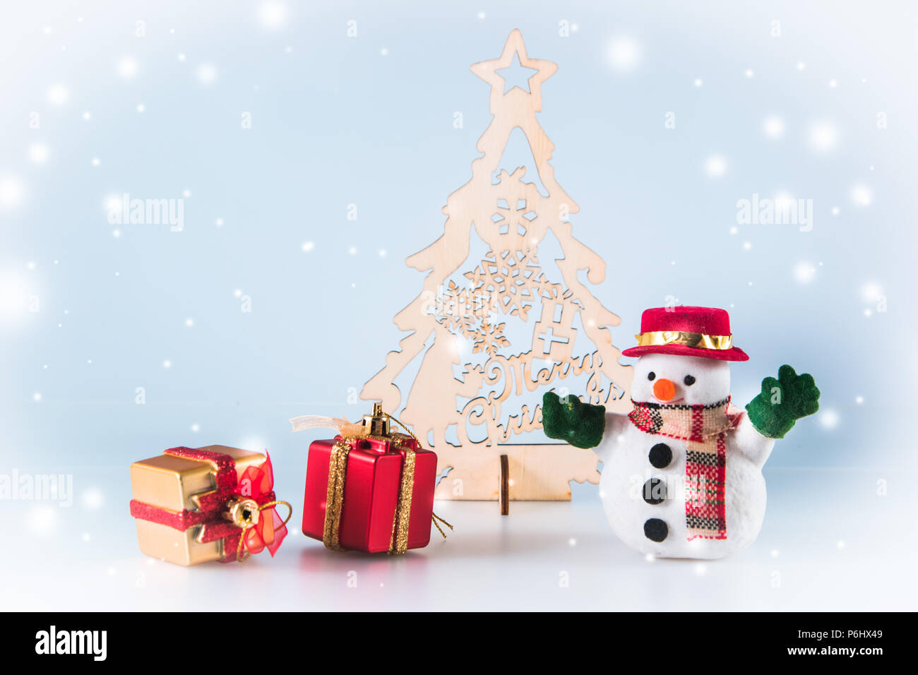 Snowman And Gift Box Stand Near Christmas Tree On White Background
