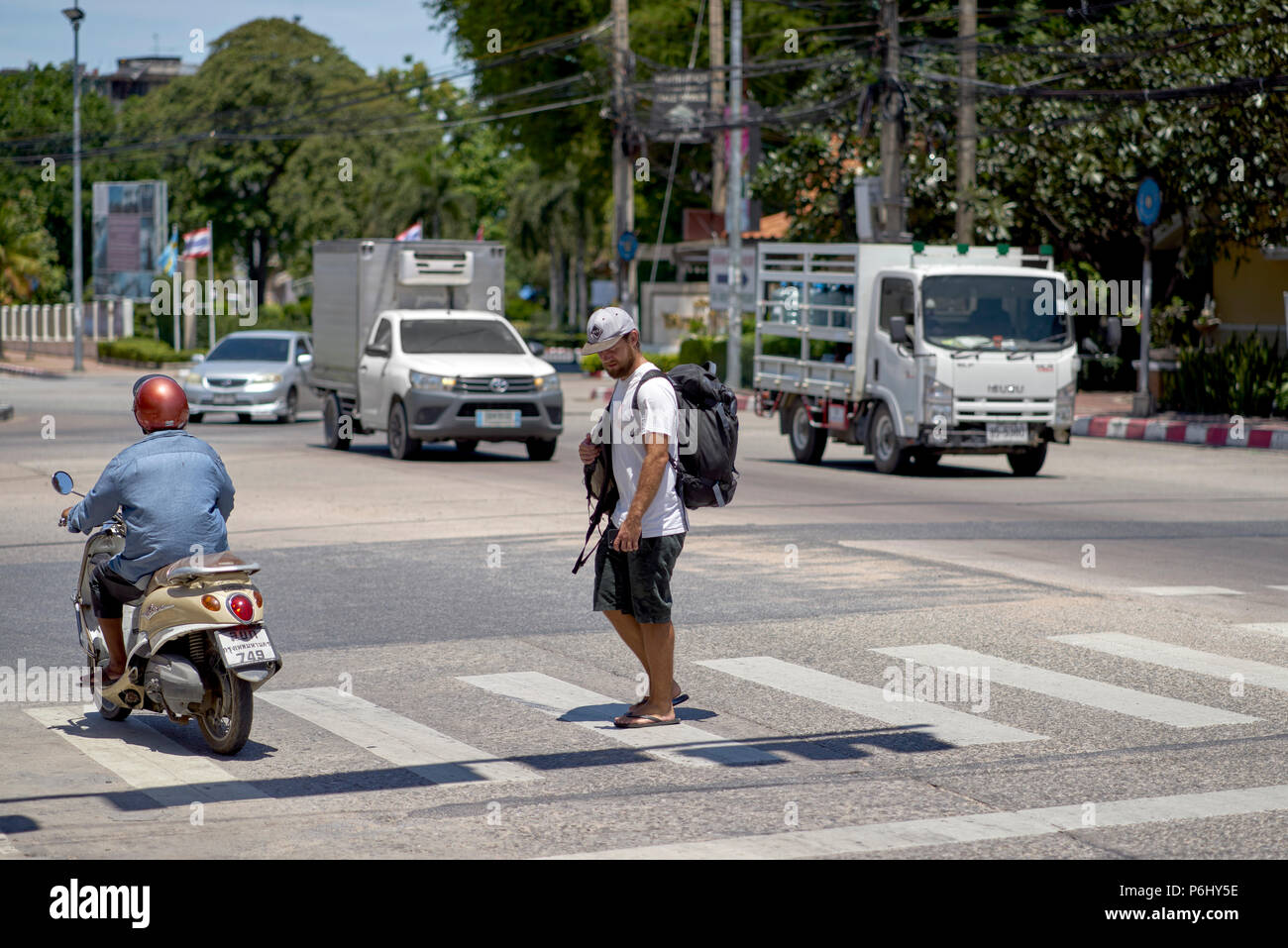 Man using the pedestrian crossing with motorcyclist ignoring his right of way which is common amongst Thai motorists. Thailand Southeast Asia - Stock Image