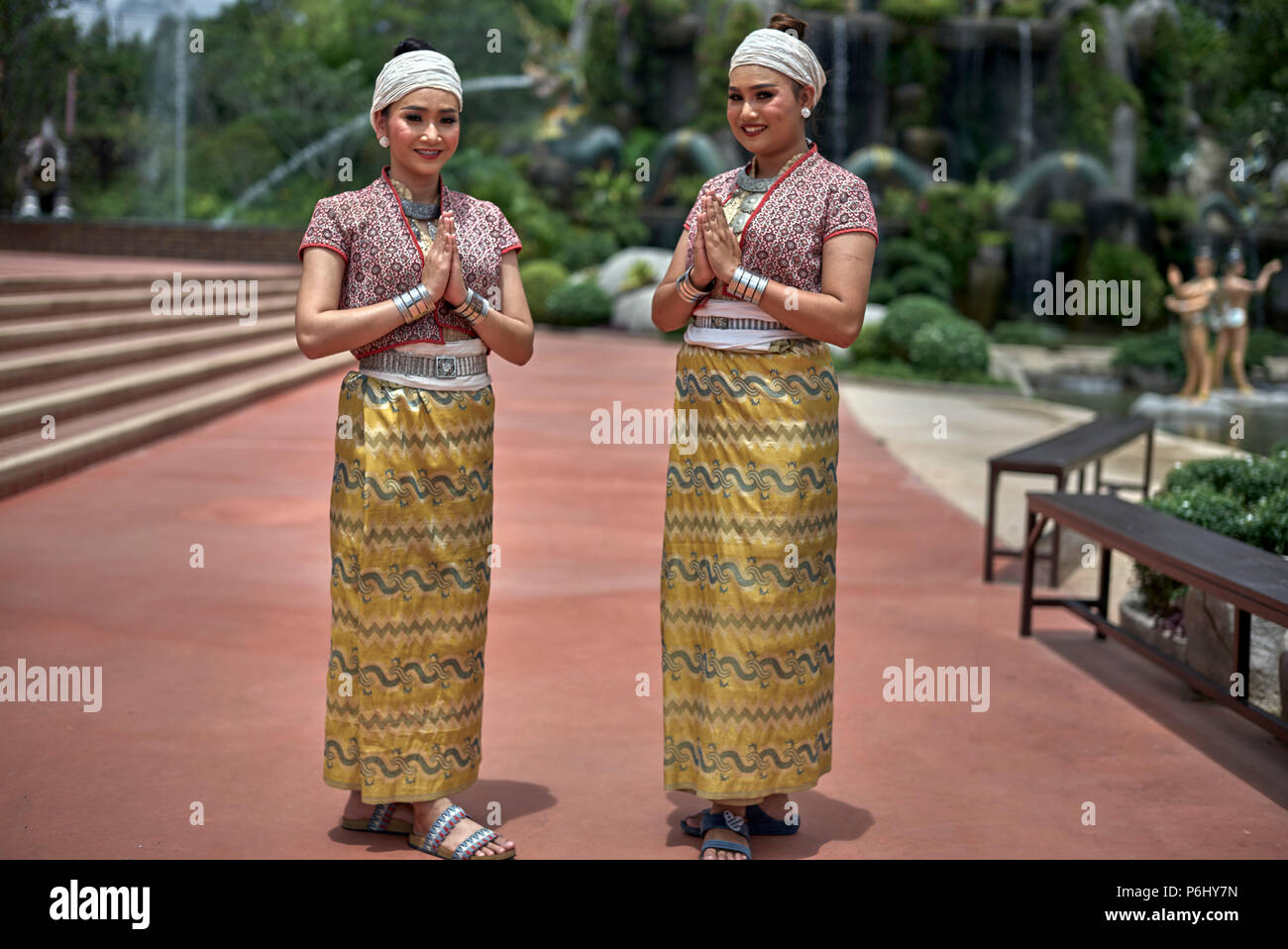 Thailand women in traditional dress and showing respect and greeting with the customary Thai Wai - Stock Image