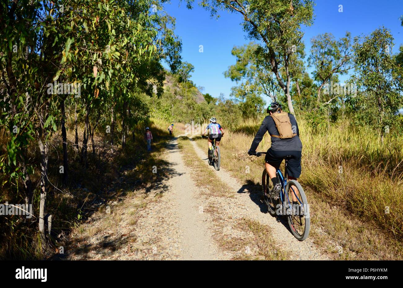 Two retiree bike riders riding on a dirt road, Many peaks hike to Mount Marlow, Townsville Town Common Queensland, 4810, Australia - Stock Image