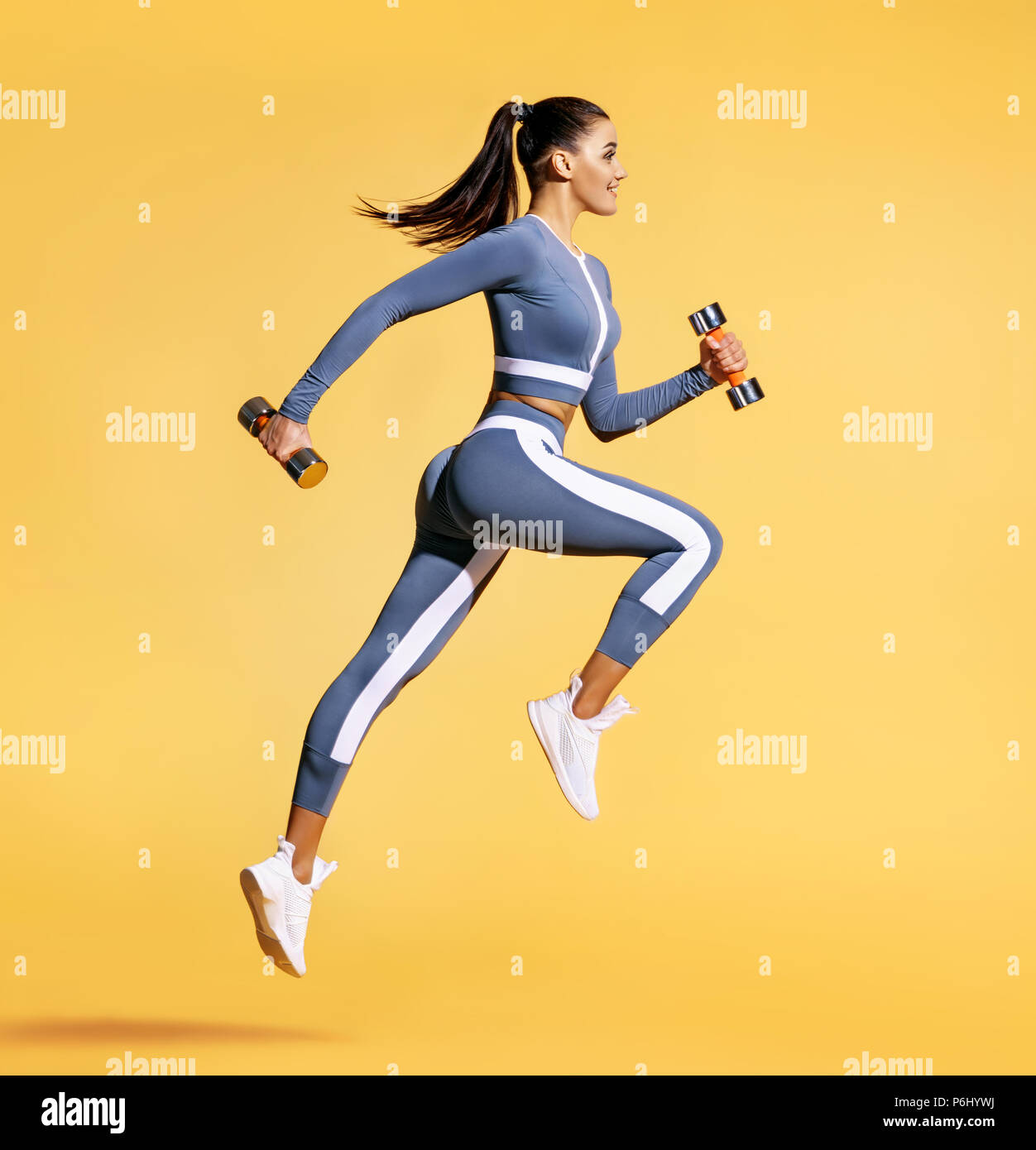 Sporty woman jumping with dumbbells. Photo of active woman in sportswear on yellow background. Dynamic movement. Side view. Sport and healthy lifestyl - Stock Image