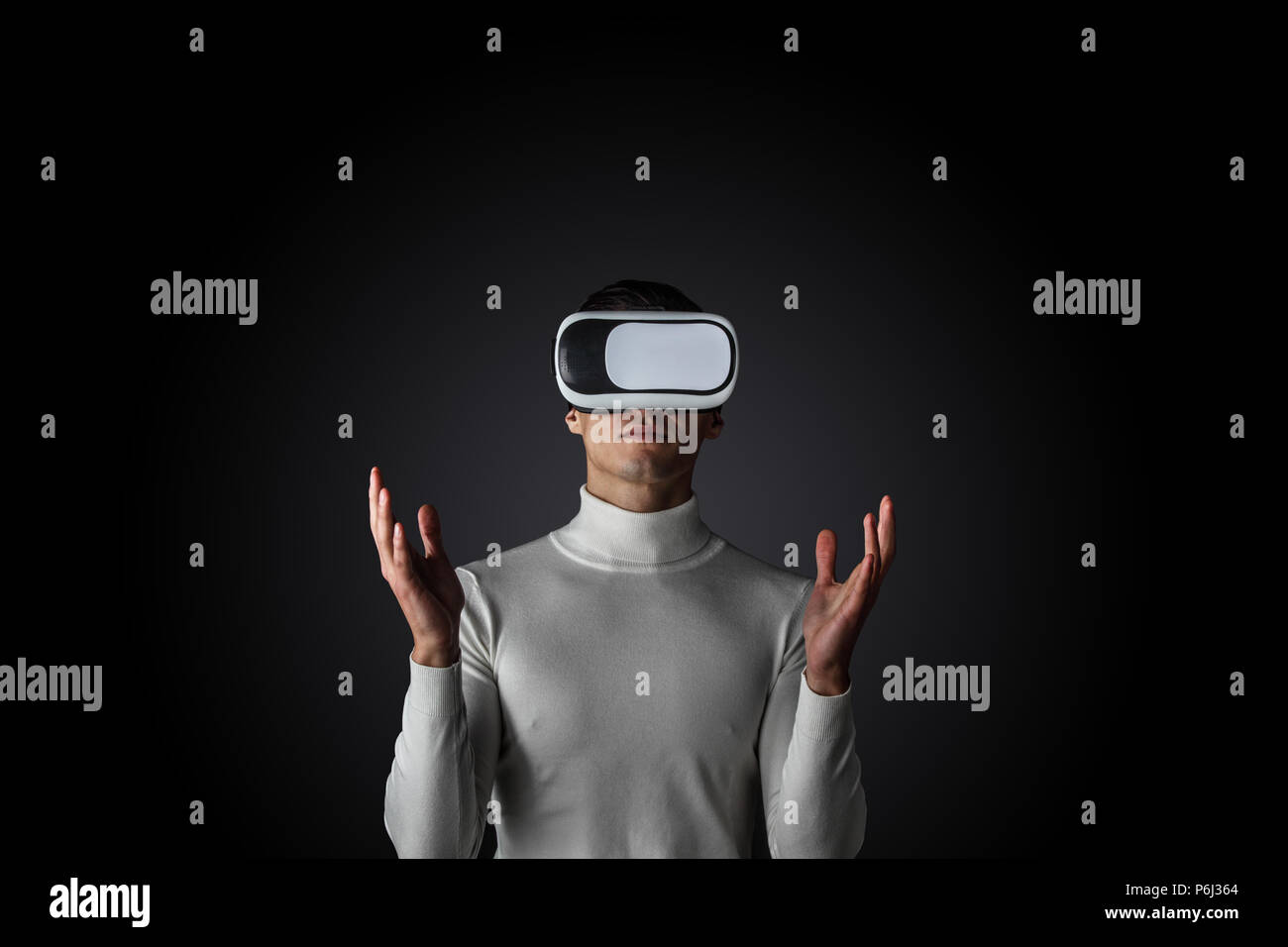 Man using futuristic VR goggles and touching virtual screen with digital pen - Stock Image
