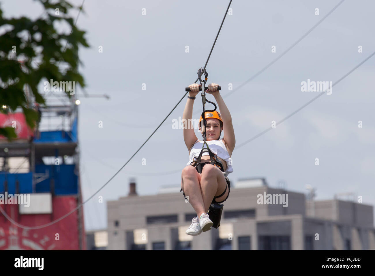Montreal Zip Lining girl with legs crossed Stock Photo