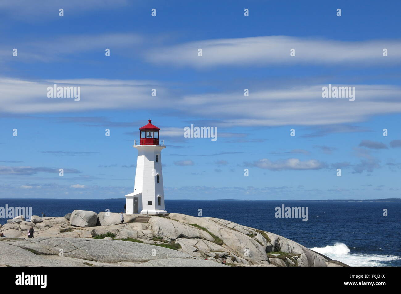 The red and white lighthouse on an outcrop of granite boulders at Peggys Cove, Nova Scotia, Canada - Stock Image