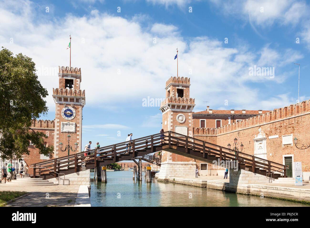 Entrance to the Arsenale, Castello, Venice, Italy on Rio de l'Arsenal with tourists on Ponte de l'Arsenal o del Paradiso bridge, Medieval Naval shipya - Stock Image