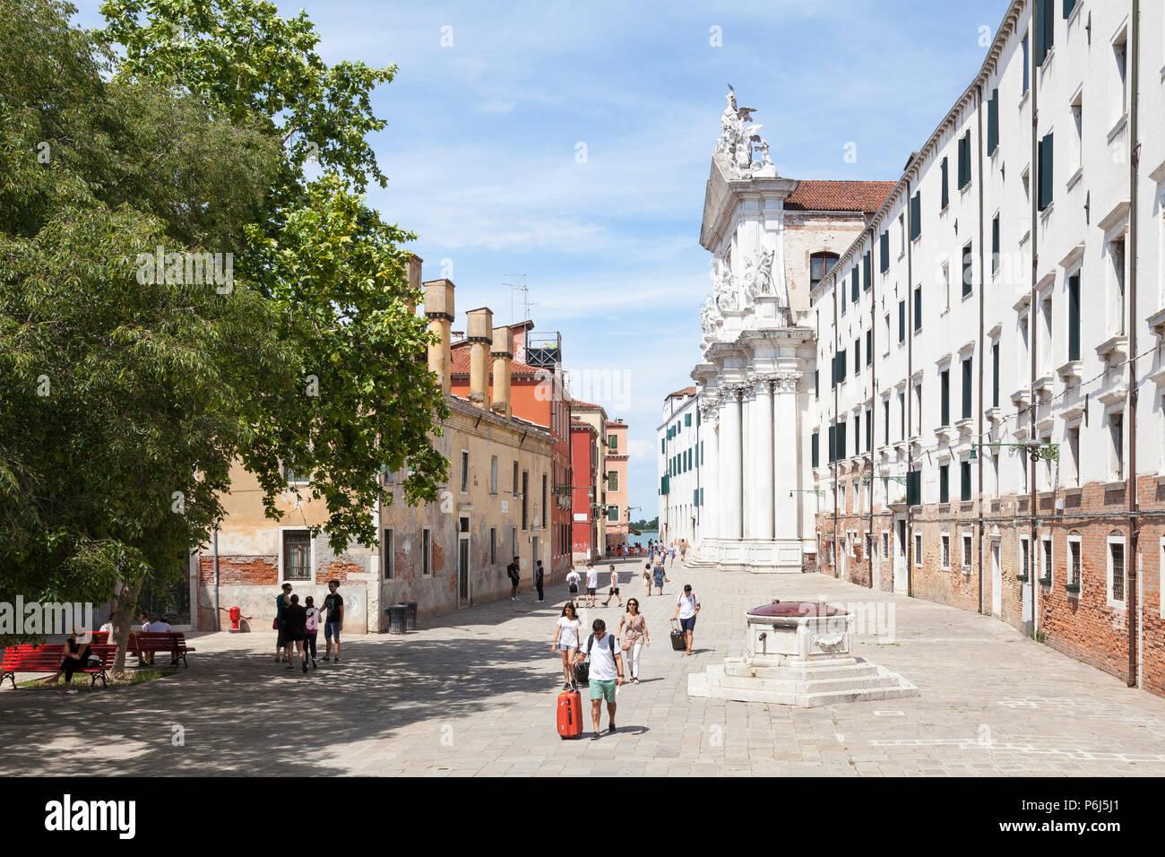 Gesuiti Church, Campo dei Gesuiti,  Cannaregio, Venice, Veneto, Italy with tourists walking with luggage past the ancient pozzo (well head) - Stock Image