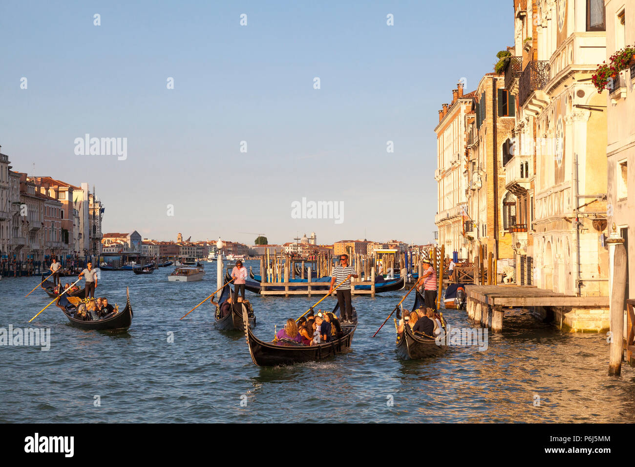 Tourists enjoying romantic  gondola rides at sunset on the Grand Canal, Venice, Veneto, Italy. Golden hour with reflections. - Stock Image