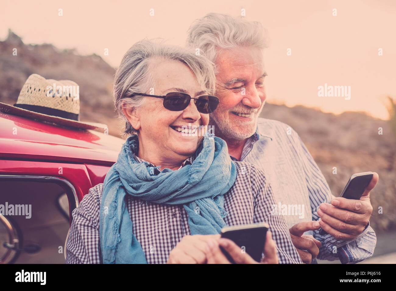 Elderly couple with hat, with glasses, with gray and white hair, with casual shirt, on vintage red car on vacation enjoying time and life. With a chee - Stock Image