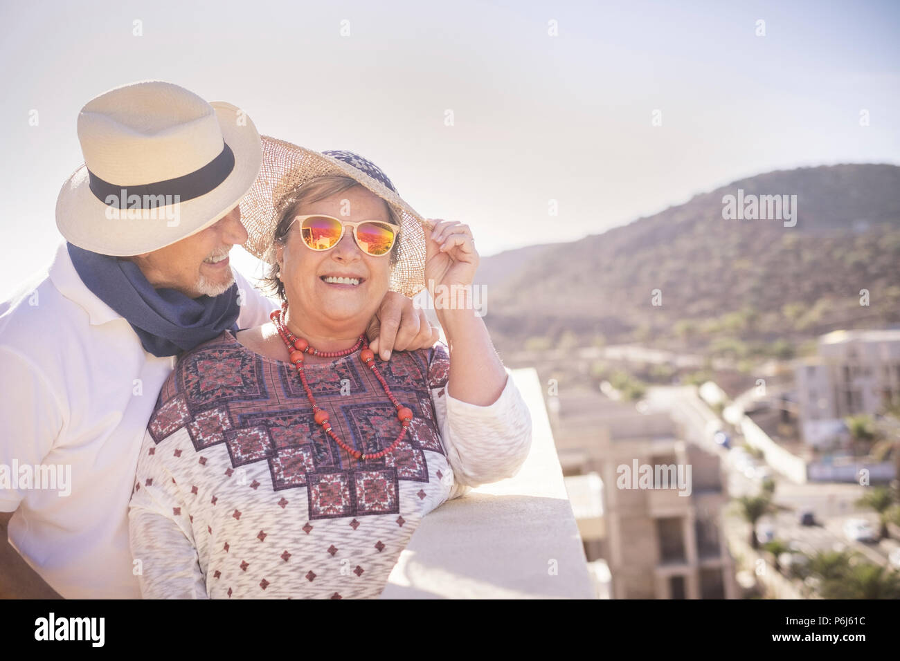 beautiful couple of senior elderly adult people smiling and enjoying leisure outdoor time in the summer. terrace rooftop with buildings in constructio - Stock Image