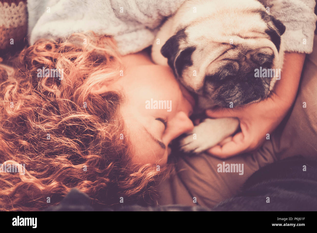 real true love between middle age beautiful woman caucasian sleeping and protect, her best friends dog pug. friendship and relationship at home in the Stock Photo