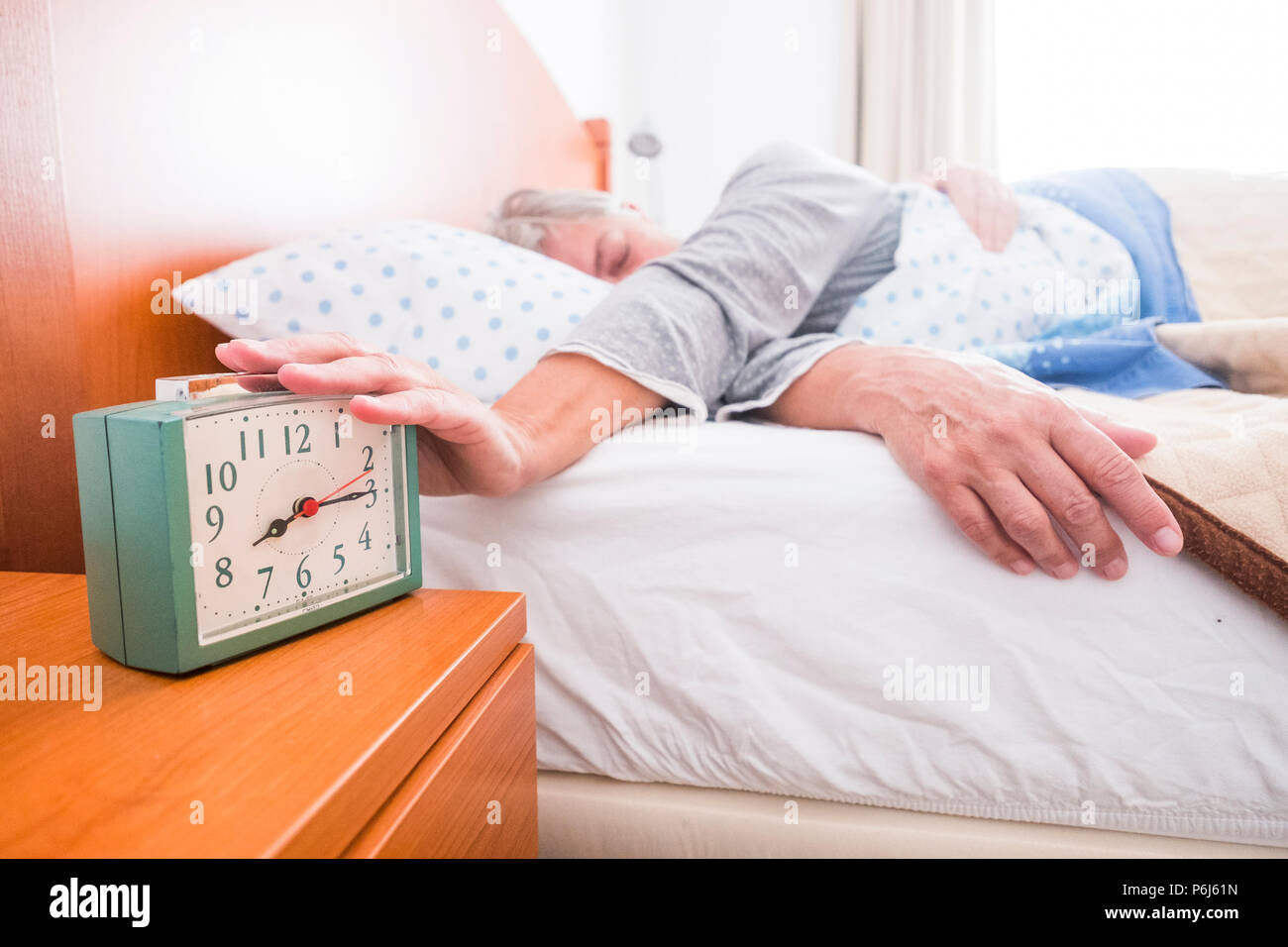 waking up stop alarm daily scene for adult woman caucasian in the morning at home. don't want to go office but retired live. lazy and tired people. cl - Stock Image