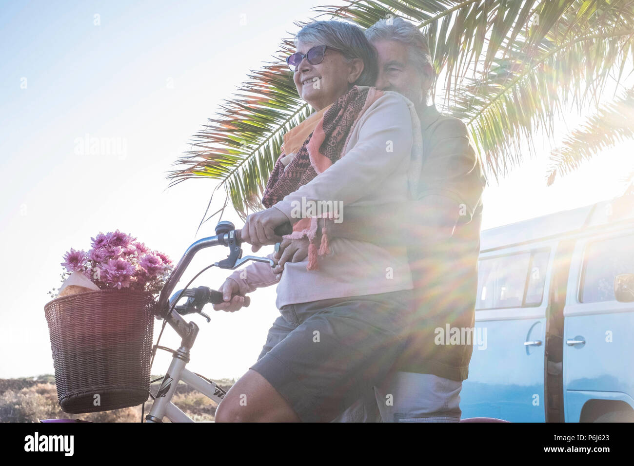 elderly senior caucasian couple play and enjoy leisure activity outdoor in lifestyle vacation. man and woman retired go on a vintage bike like childre - Stock Image