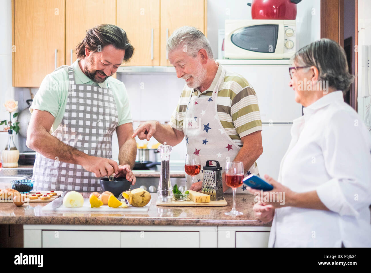 caucasian family three man people cook together lokking the how to do on the mobile phone of the mother. everybody have fun and laugh preparing someth - Stock Image