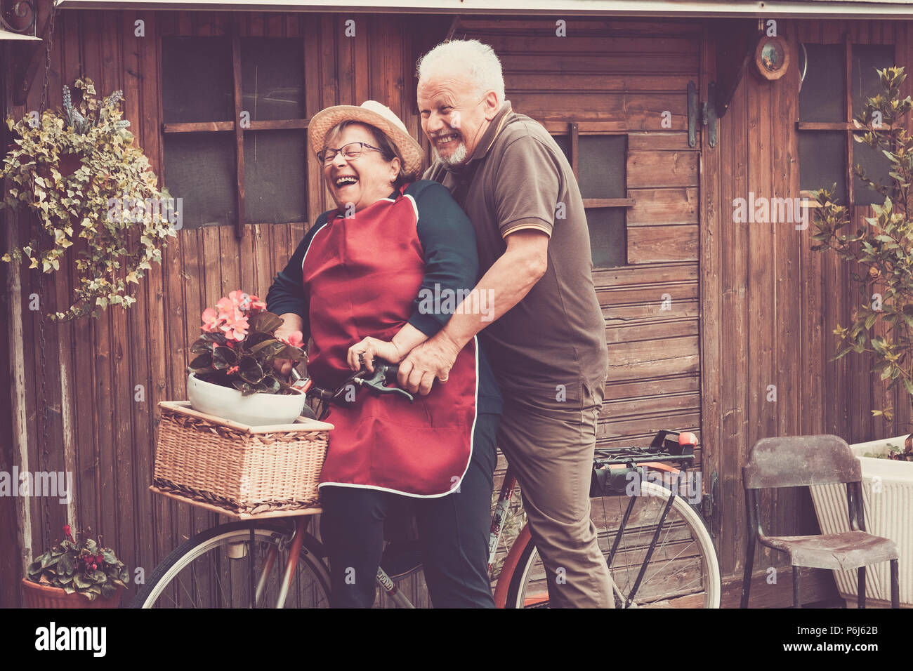 Nice caucasian people enjoy leisure outdoor both on a single bike lauhing like crazy. together funny moments at home outside. vintage filter and color - Stock Image