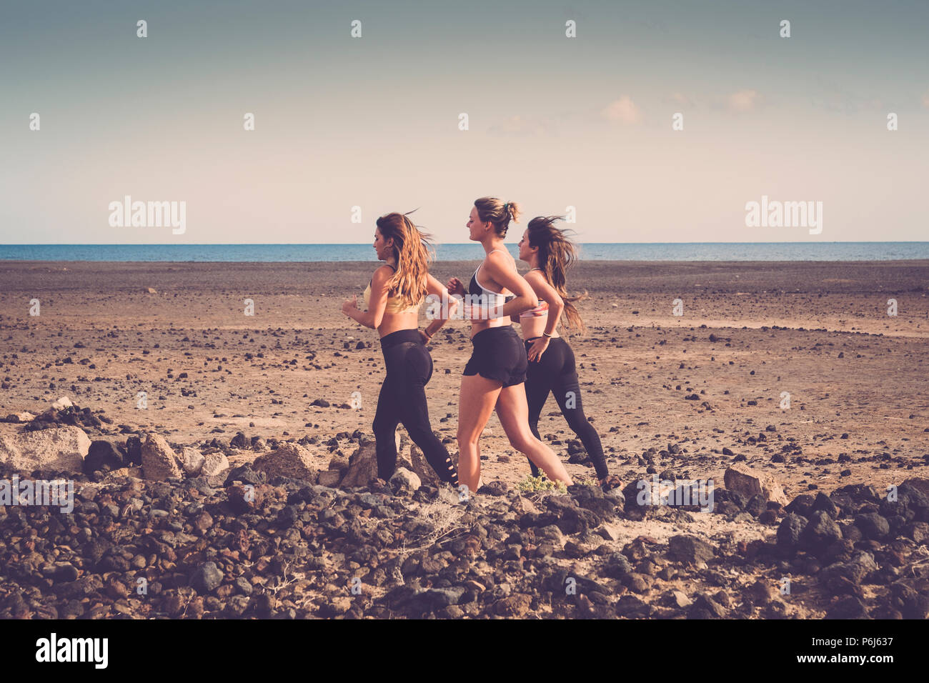 group of three young beautiful women run near the beach in outdoor nice location with blue ocean in background. Healthy people do exercises to build a - Stock Image
