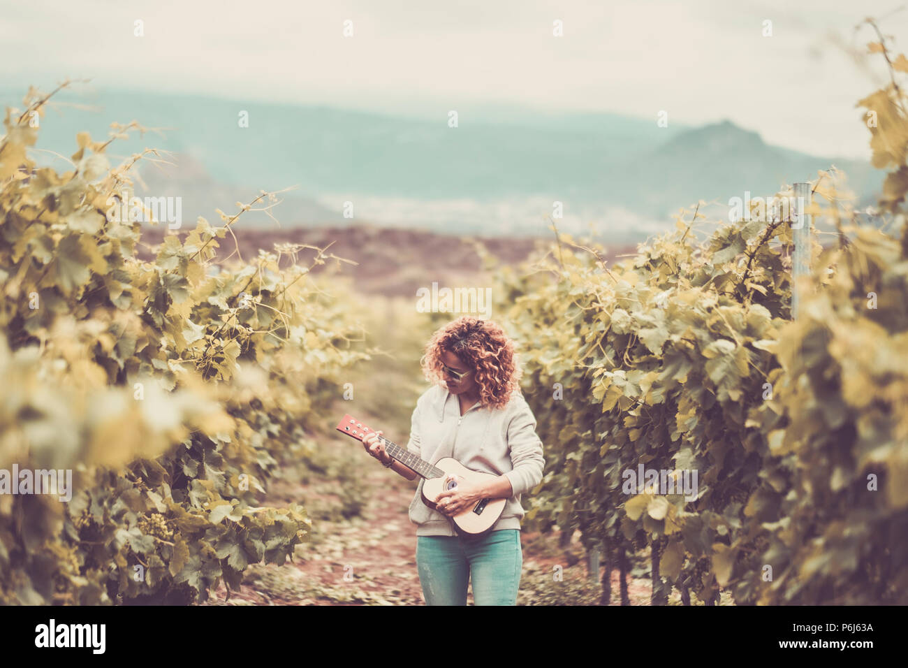 nice beautiful caucasian woman walk alone in the vineyard green background singing an ukulele acoustic guitar. freedom alternative lifestyle hippy con - Stock Image