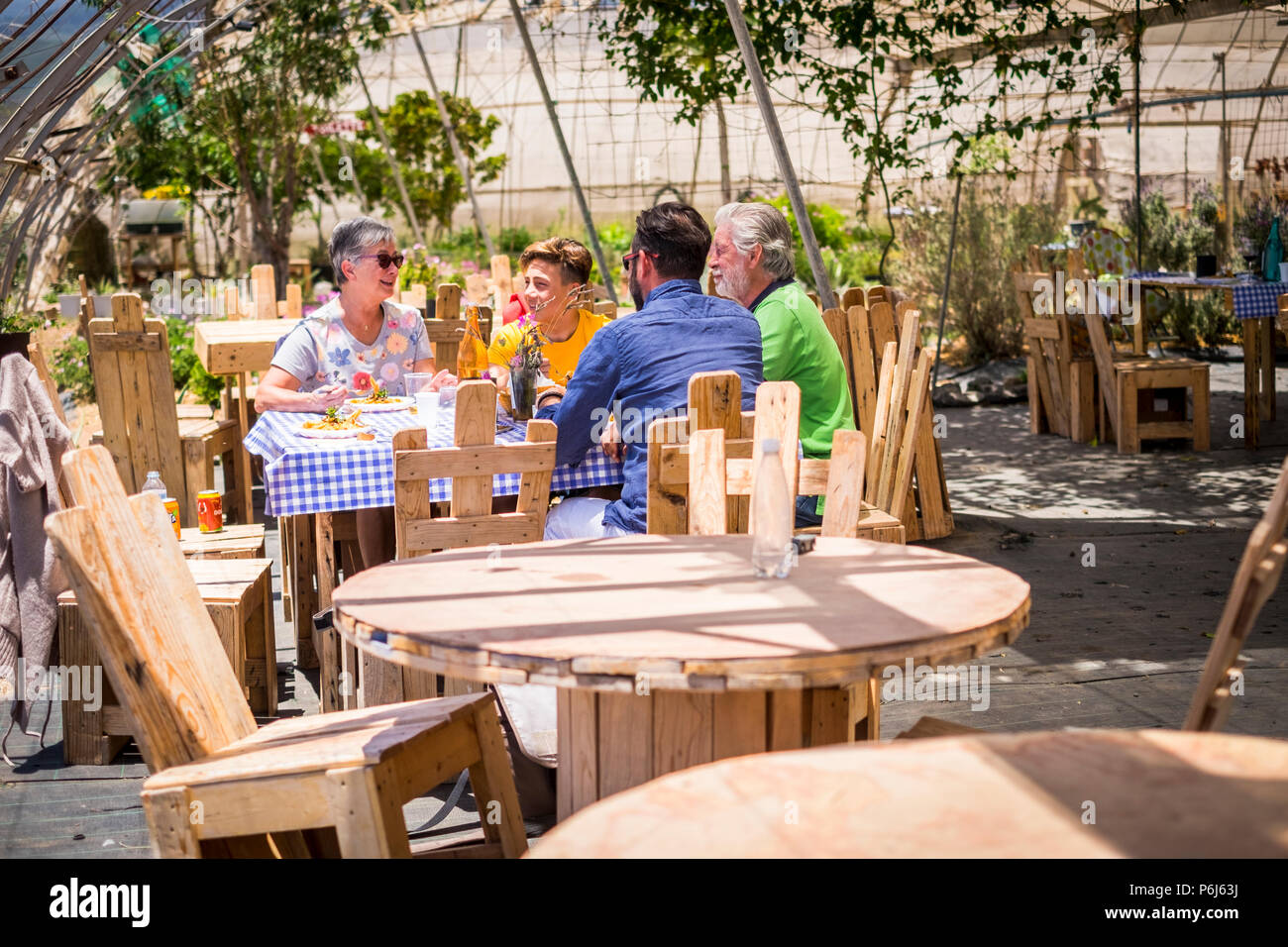 family at lunch together outdoor natural scenic place with a lot of recycled wood furnitures made with pallets. enjoy and smile leisure activity cauca - Stock Image