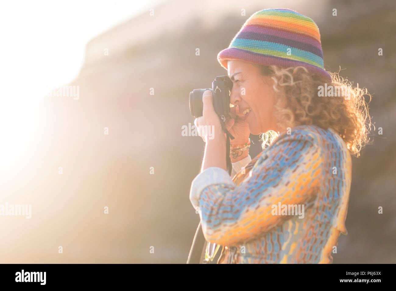 woman caucasian photographer with nice coloured hat taking pictures with old little camera. sunlight and sun flare in the background. bright summer co - Stock Image