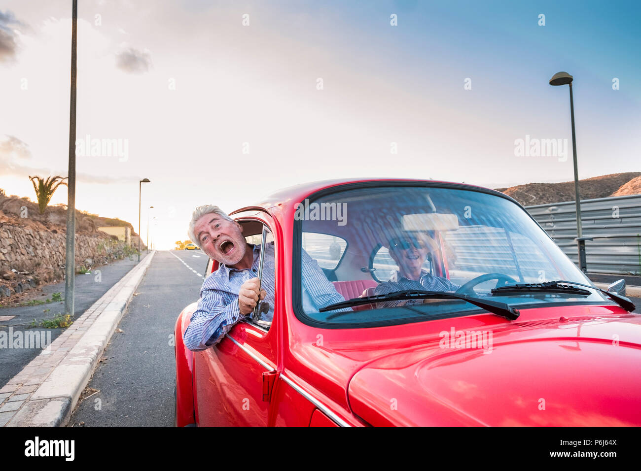 nice beautiful senior adult couple traveling together while the woman drive and the man shout for scare or for craziness. happiness and joy together f - Stock Image
