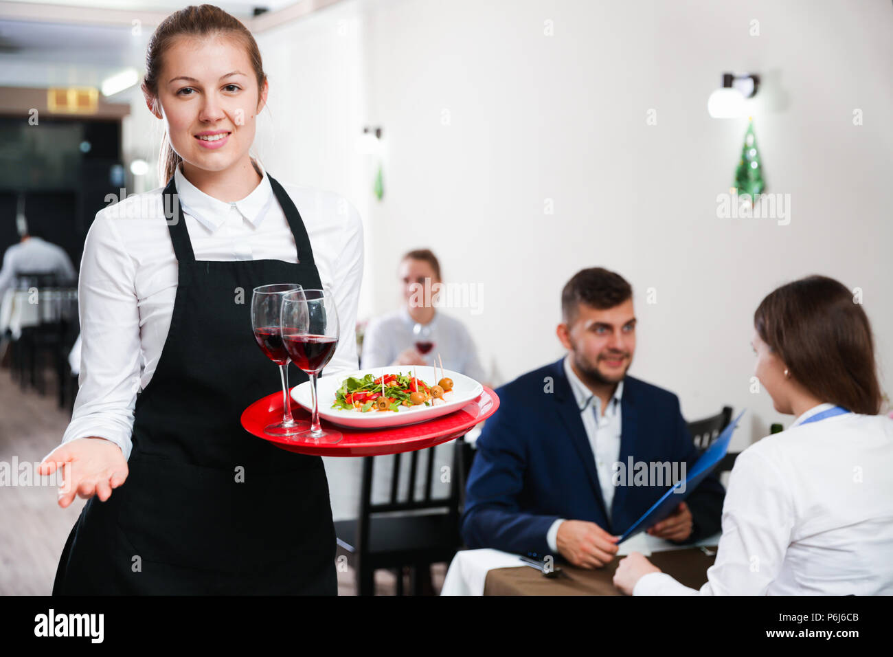 Affable female waiter is standing with order in luxury restaurante indoor. - Stock Image