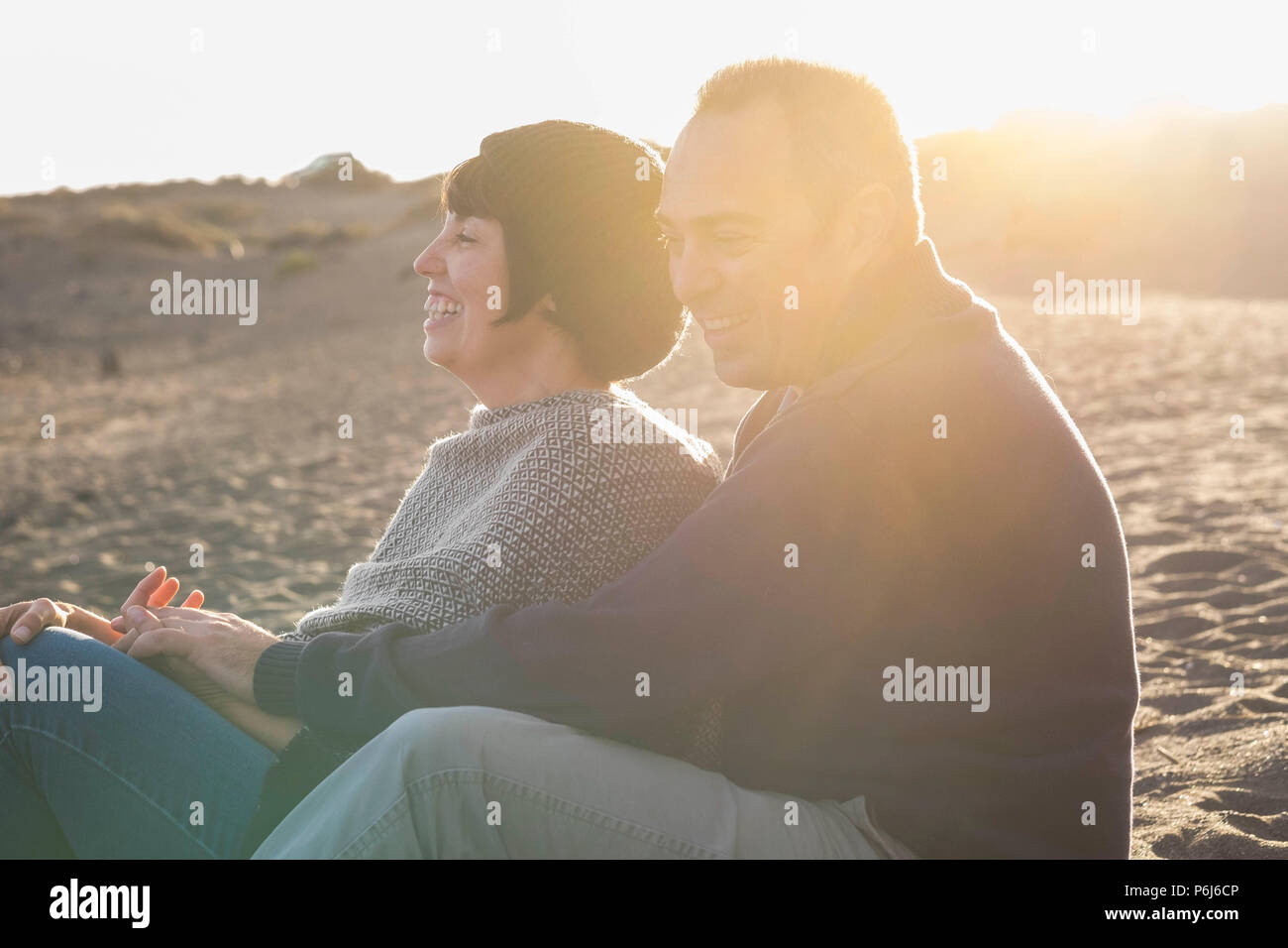 nice caucasian people couple have fun and smiles and laugh together during a golden sunset with backlight on the beach in vacation or lesiure activity - Stock Image