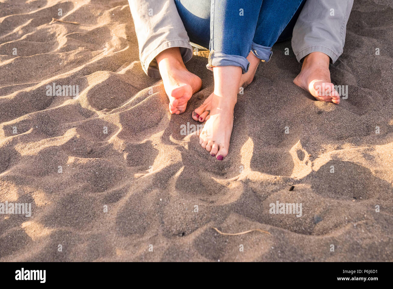 hugged feet in a summer sunny day at the beach for vacation or leisure activity together in couple. love and relationship concept with man and woman t - Stock Image