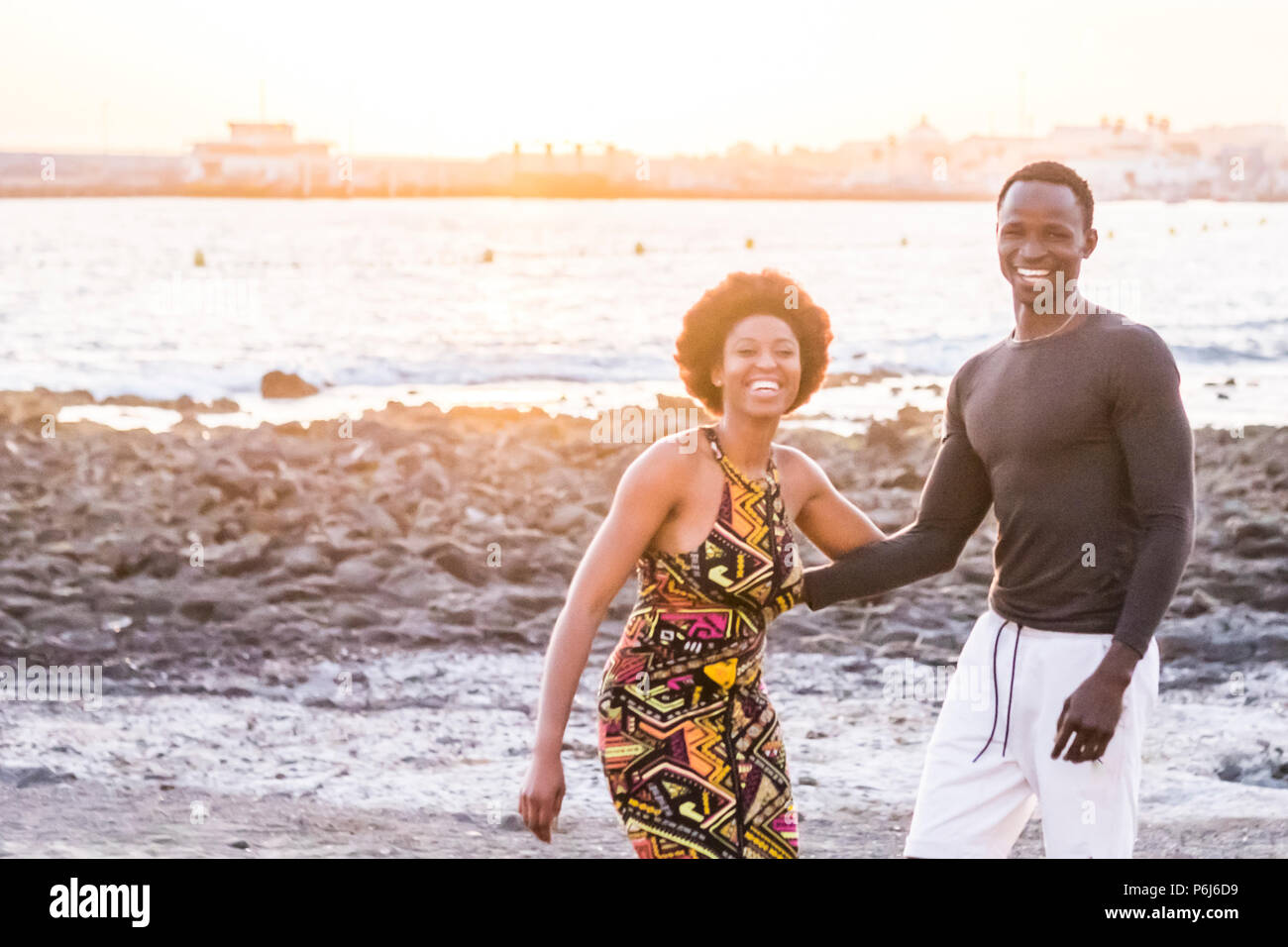 Happy black african race skin couple together having fun at the beach in vacation. happiness concept with two young man and woman having fun together. - Stock Image