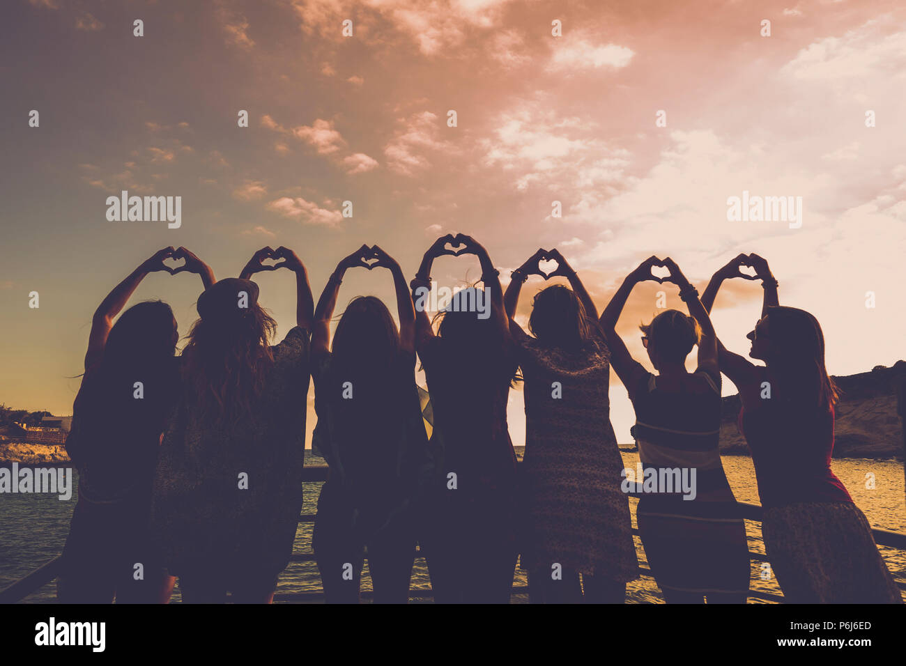 romantic concept for girls doing hearts with hands all together in relationship and friendship in front of a beautiful sunset and the ocean. golden to - Stock Image