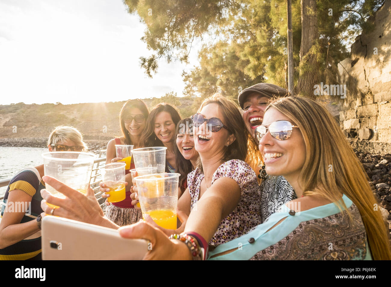 group of young beautiful caucasian woman taking selfie in vacation leisure activity outdoor near the beach and the ocean. sunset time with backlight a - Stock Image
