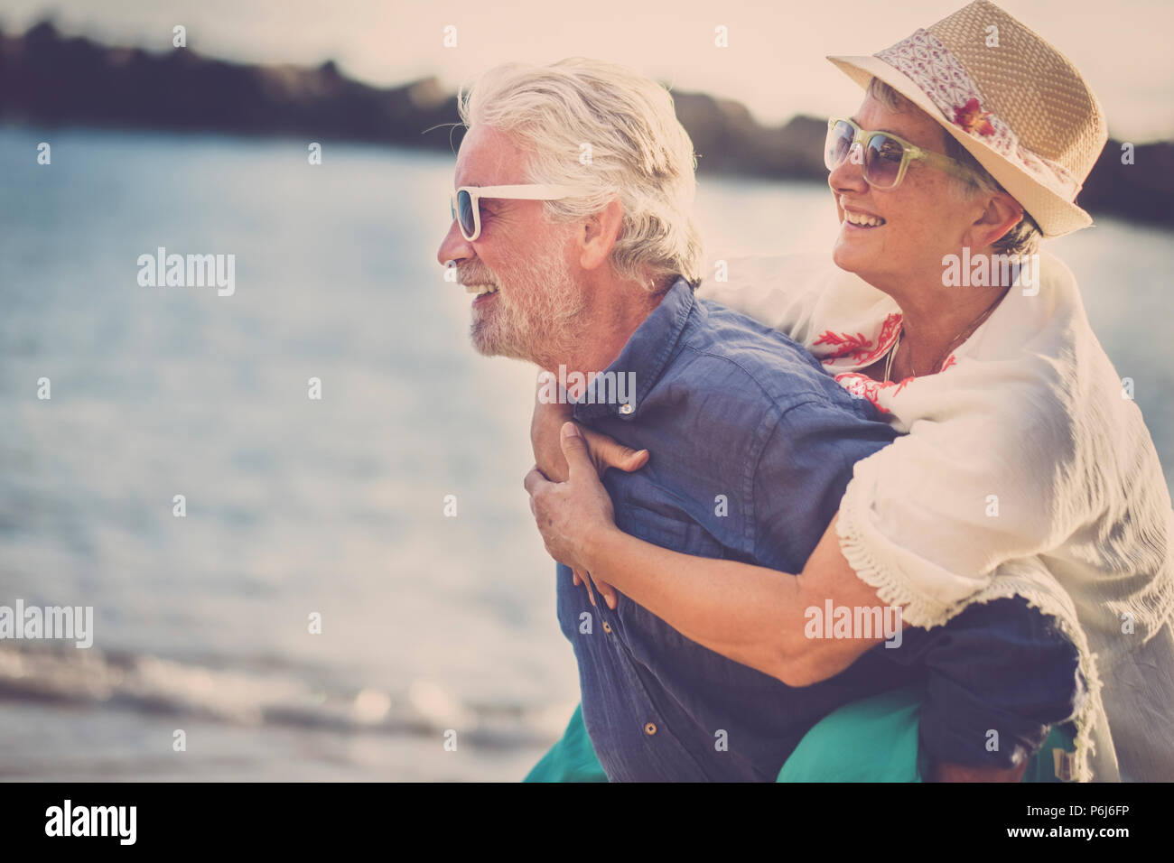 happy senior couple have fun and enjoy outdoor leisure activity at the beach. the man carry the woman on his back to enjoy together a retired lifestyl - Stock Image