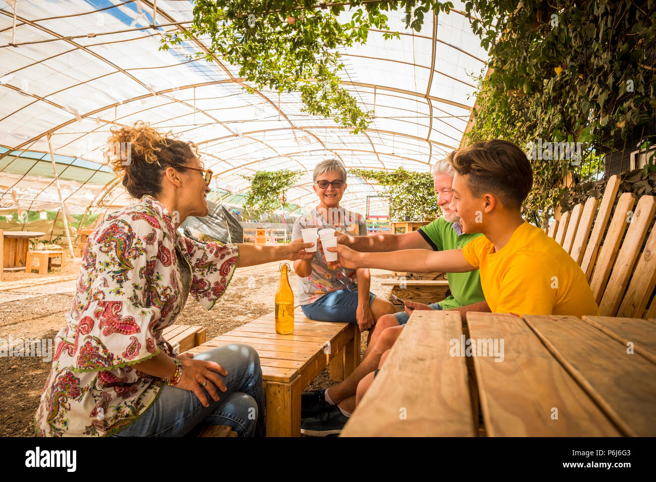 family drinking and cheers together in outdoor leisure activity in a restaurant made by recycled wood and in respect with the nature. everybody smile  - Stock Image