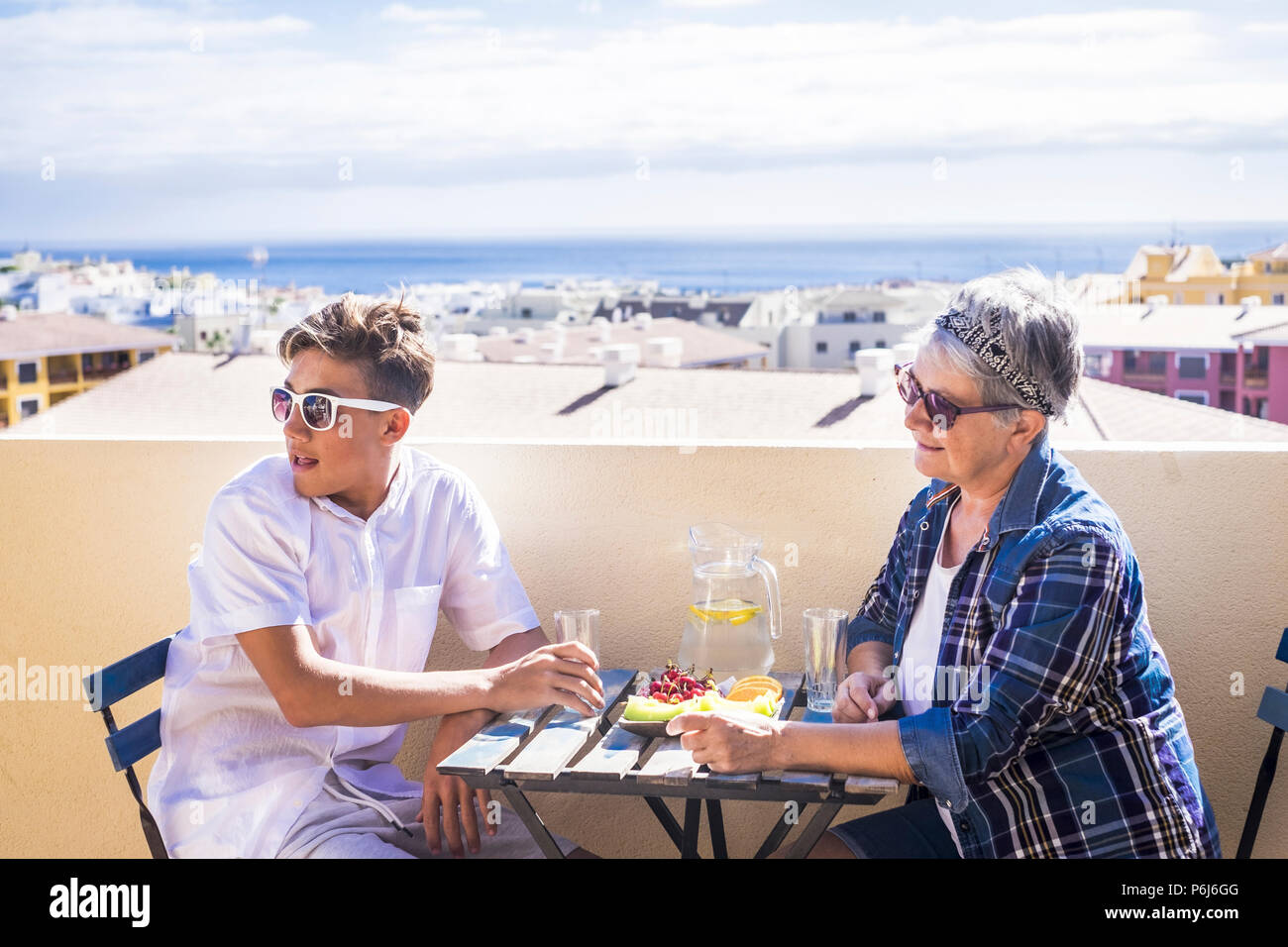couple young and old people woman and boy grandmother and nephew for family concept lifestyle leisure activity eating something on the terrace rooftop - Stock Image