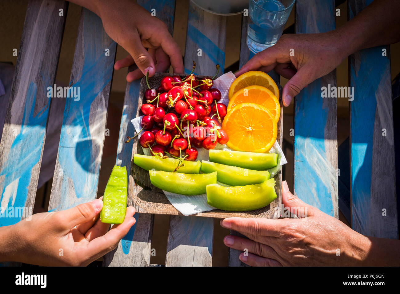 closeup of young and old hands from grandmother and teenager nephew eating some fresh season fruits on the wood table. healhty lifestyle in family out - Stock Image
