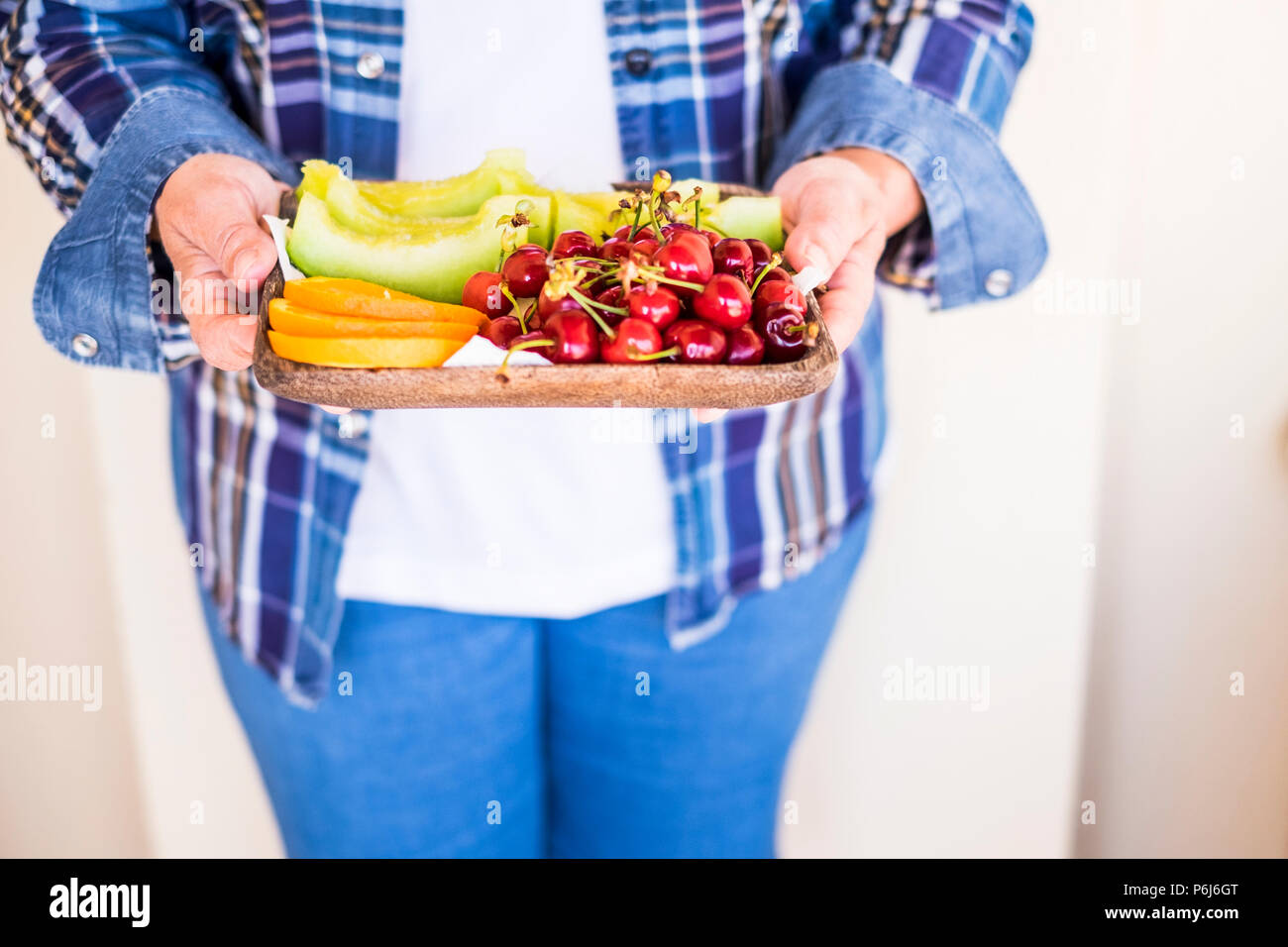 old caucasian woman senior caucasian in casual jeans clothes offer some fresu seasonal fruits to you. melon, orange and cherry for a mixed colors food - Stock Image