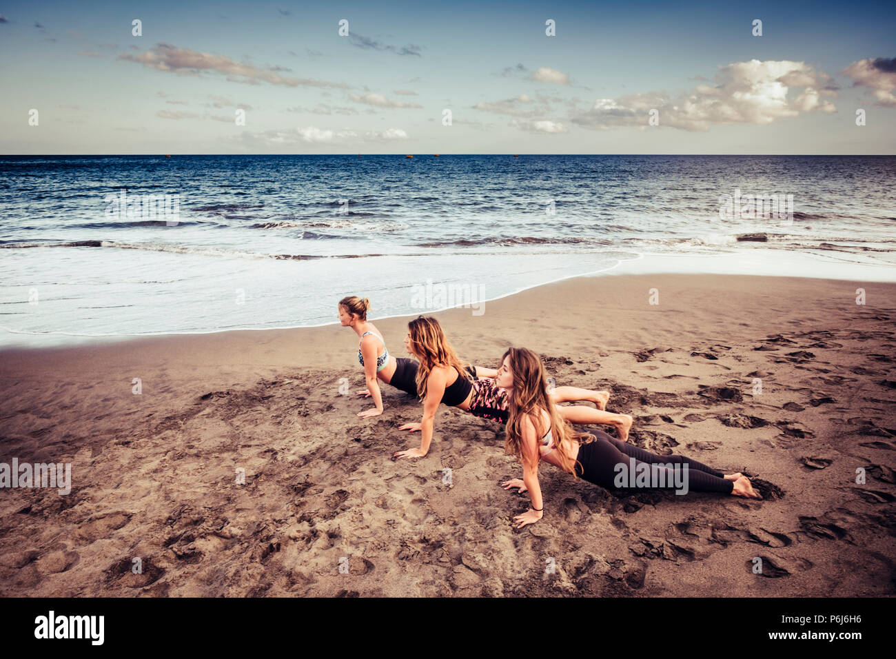Three cacuasian young ladies doing pilates on the shore near the  waves and the ocean. outdoor leisure activity sport and lifestyle fitness for beauti - Stock Image