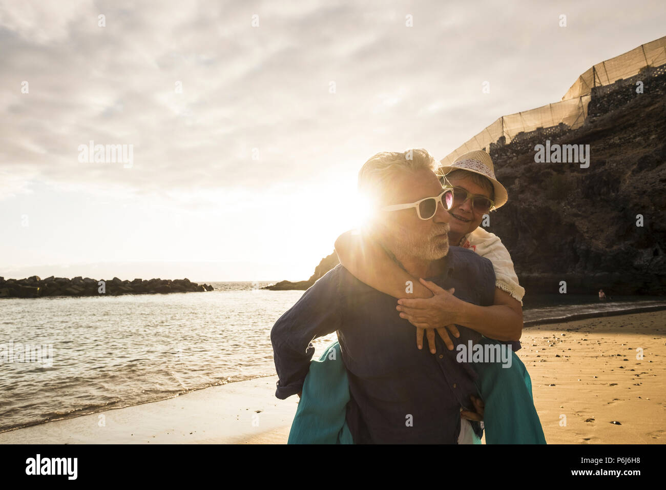 Happy senior adult caucasian couple in love. the man carry on his back the beautiful woman and both smiles. affective and together forever life concep Stock Photo